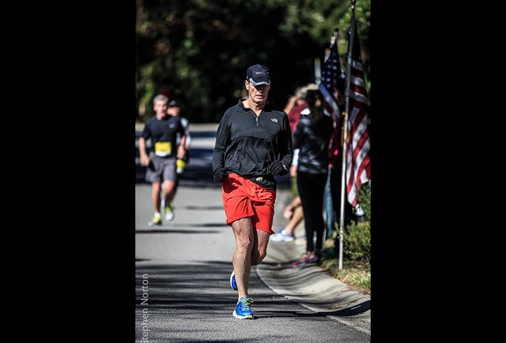 Dr. Pate running next to American flag