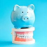 Piggy bank resting on top of a model of teeth