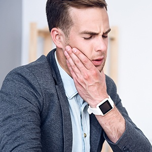 Man holding jaw in pain
