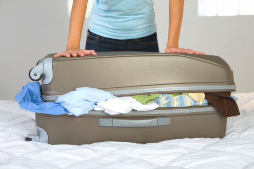 Woman closing overloaded suitcase
