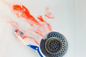 blood and toothpaste going down sink drain