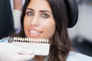A dentist comparing porcelain veneers to a patient's smile.