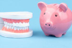 Set of teeth next to pink piggy bank