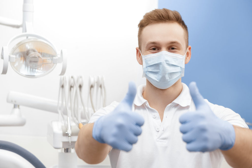 A hygienist practices social distancing in dentist offices.